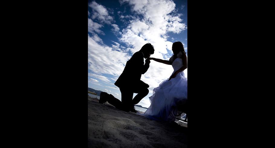 foto del baciamano dello sposo alla sposa sulla spiaggia dopo le loro nozze